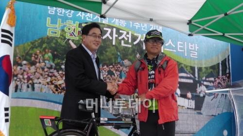 ▲ 자전거 전달식을 하는 김선교 군수와 최형규 대표(왼쪽부터)