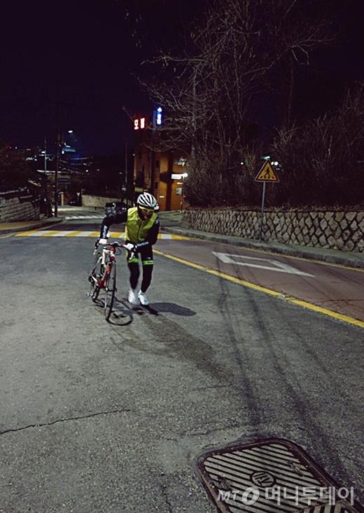 자전거동호인이 자전거를 끌고 가파른 언덕을 오르고 있다./사진=이고운 기자