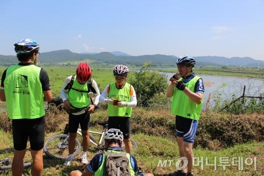 초평도를 배경으로 휴식 중인 참가자들/사진=박정웅 기자