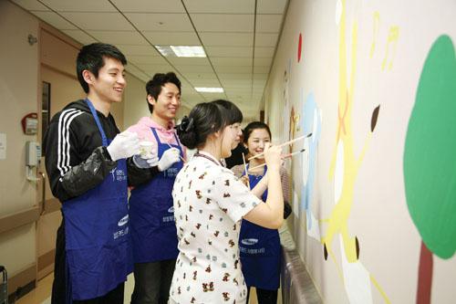 삼성카드 직원들이 서울 고대구로병원 어린이 병동에 벽화를 그려주는 봉사활동을 진행하고 있다.
