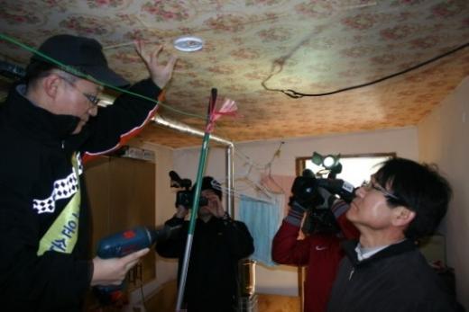 롯데건설 직원이 단독경보형감지기를 설치하고 있다.(사진제공=롯데건설)