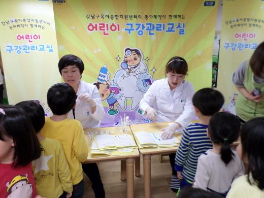 동아제약이 운영하는 어린이 구강관리교실에서 치위생사가 어린이들의 구강검진을 하고 있다.