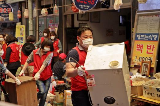 광주신세계 임직원들이 지난해 5월 광주 동구 대인시장에서 천원백반을 팔다 영업 중단에 처한 한 식당에서 수리 및 영업환경 개선활동을 벌이고 있다.