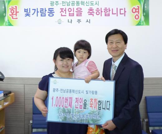 김원채 빛가람동장이 1000번째 전입주민인 이혜경에게 꽃다발을 전달하며 환영하고 있다.