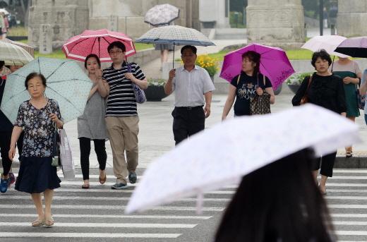 소나기가 내린 지난 19일 오후 서울 서대문구 독립문사거리에서 시민들이 우산을 핀 채 걸어가고 있다/사진=서울 뉴스1 민경석 기자