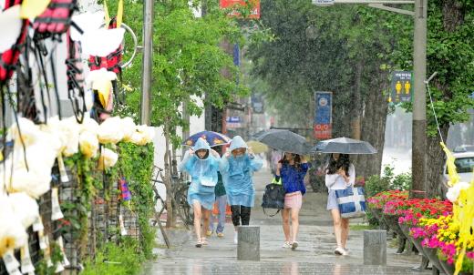전북 전주시 전동 앞에서 관광객들이 비를 피해 우비를 입고 뛰어가고 있다. /자료사진=전주 뉴스1 김대웅 기자