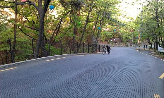 한 자전거 동호인이 자전거를 끌고 도선사로 향하는 삼양로173길을 힘겹게 오르고 있다./사진제공=김종상
