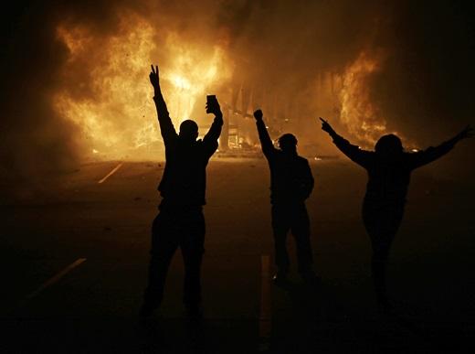 미국 대배심이 24일 18살의 비무장 흑인 청년 마이클 브라운을 사살한 백인 경찰 대런 윌슨을 기소하지 않기로 결정한데 항의하는 시위가 격화되는 가운데 미주리주 퍼거슨에서 시위대가 불타는 상가 건물을 바라보고 있다. /사진=뉴시스