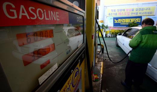 국제 유가 하락으로 휘발유 가격 하락세가 이어지고 있는 가운데 서울 광진구의 한 주유소에서 직원이 차량에 주유를 하고 있다. /사진제공=뉴스1 박정호 기자