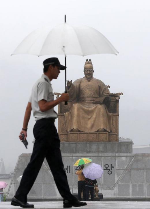 비오는 날 우산 쓴 경찰이 세종대왕상 앞을 지나고 있다./사진=뉴스1