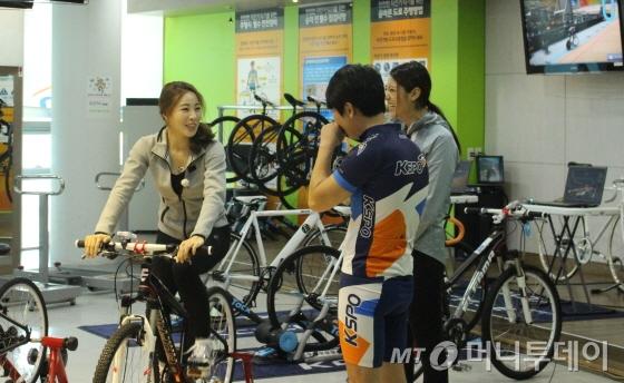 신수지(좌측)가 국민체육진흥공단 관계자의 설명을 들으며 자전거 고정롤러 체험을 하고 있다./사진=박정웅 기자