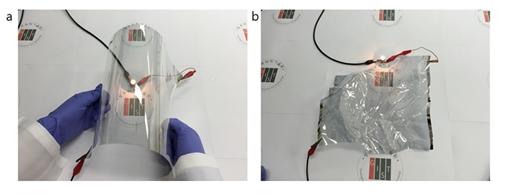 A4 크기의 플렉시블 투명전극의 유연성을 보여주는 실험 모습이다. 휘어진 상태(a)에서도 전구가 켜지며, 같은 투명전극을 종이처럼 구긴 후(b)에도 정상적으로 작동하는 것을 볼 수 있다. /사진=미래창조과학부 제공