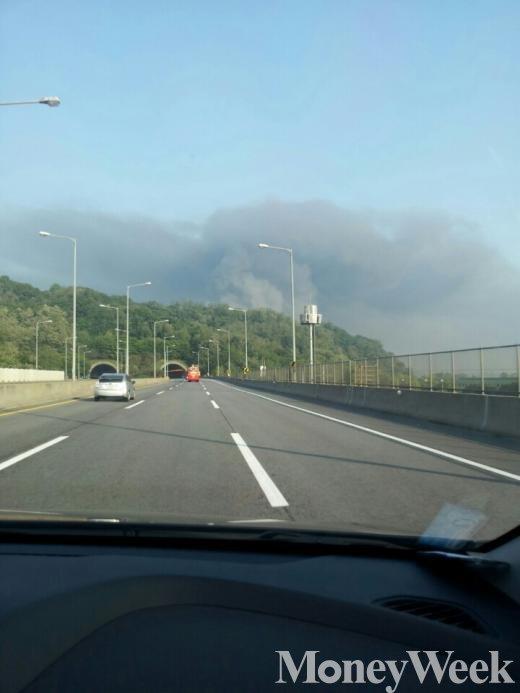 ▲김포 제일모직 물류창고에 화재가 발행했다. 마치 먹구름 처럼 현장을 덮은 연기가 보인다. (사진=독자 박현창씨 제보)