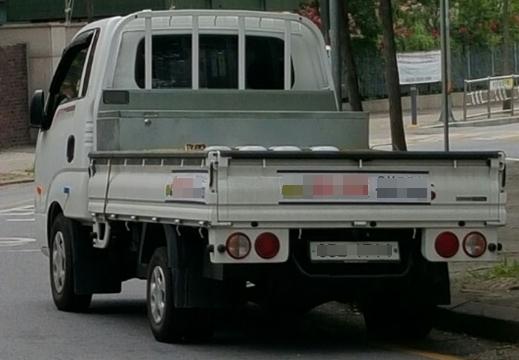 한 화물차가 중소택배사의 로고를 달고 길에 서있다. 번호판은 하얀 번호판을 달고 있다.