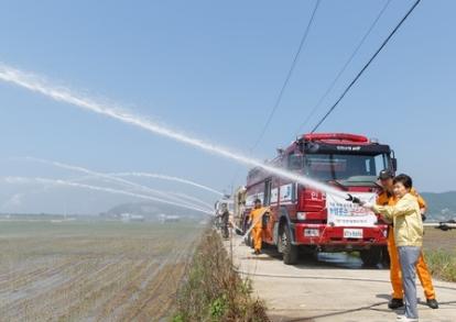 박근혜 대통령이 지난 21일 가뭄 피해지역인 경기 강화도를 찾아 급수호수를 잡고 논에 물 대는 작업을 돕고 있다. /사진=뉴스1