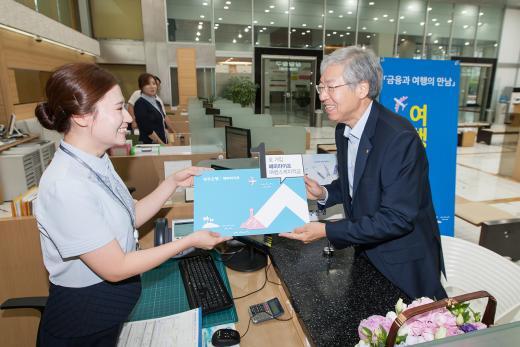 광주은행 김 한 행장이 13일 출시한 여행목적 테마형 상품인 '해피라이프 여행스케치 적금'에 첫 번째로 가입하고 있다.