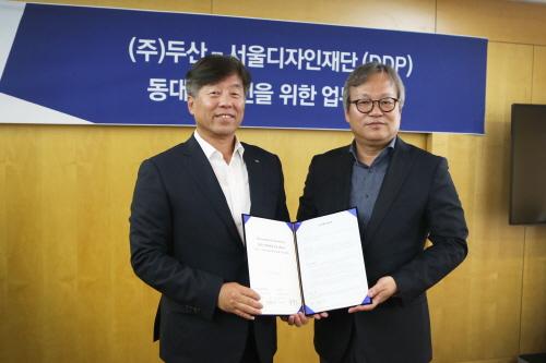 ㈜두산 사업부문 동현수 사장 (왼쪽)과 이근 서울디자인재단 대표이사가 업무협약을 체결하고 기념사진을 찍고 있다.