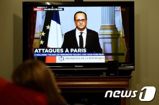프랑스에서 13일(현지시간) 총격과 폭발, 인질극 등이 잇달아 발생해 최소 60명이 숨진 가운데 프랑스 렌에서 한 시민이 TV를 통해 프랑수아 올랑드 프랑스 대통령이 프랑스 전역에 국가비상사태를 선포하는 모습을 지켜보고 있다. /사진= AFP 뉴스1 제공
