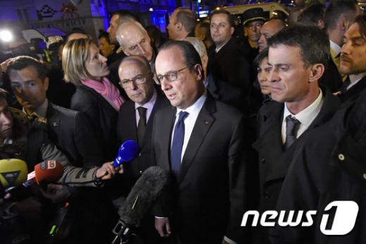 프랑수아 올랑드 프랑스 대통령(가운데)이 14일(현지시간) 베르나르 카제뇌브 내무장관(가운데), 마누엘 발스 총리(오른쪽)와 함께 파리 바타클랑 콘서트홀 인근 테러 현장에 도착해 기자들과 이야기하고 있다. /사진=뉴스1(AFP 제공)