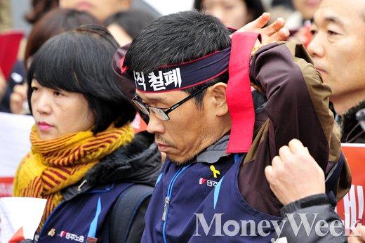 한상균 민주노총 위원장이 기자회견에 앞서 '비정규직 철폐'라고 쓰인 머리띠를 두르고 있다. /사진=임한별 기자
