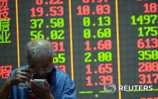중국 저장성 항저우에 있는 증권거래소 주식 전광판 앞에서 한 투자자가 휴대폰으로 주가를 확인하고 있다. /사진=뉴스1(로이터 제공)