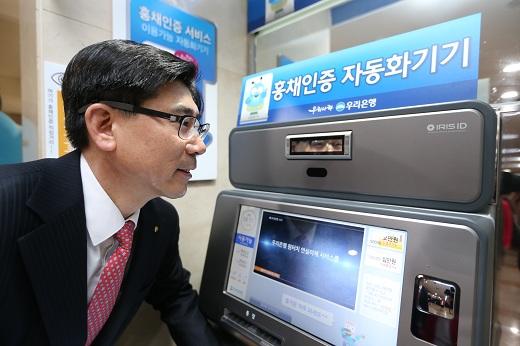 13일 오전 이광구 우리은행장이 본점영업부에 설치된 자동화기기에서 홍채인증 금융거래서비스를 시연하고 있다./사진=우리은행