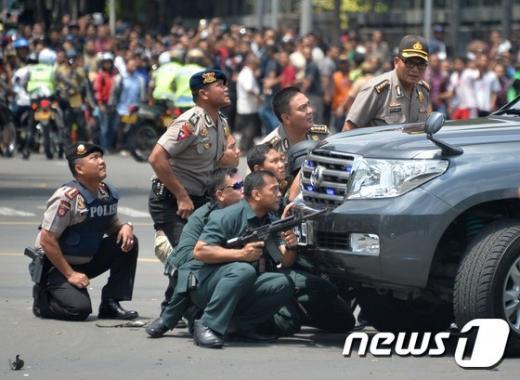 인도네시아 수도 자카르타의 도심 쇼핑몰 인근에서 14일 수차례 폭발이 발생해 최소 4명이 숨진 가운데 현지 경찰이 차량 뒤에 숨어서 상황을 지켜보고 있다. 이날 경찰과 용의자들 간에는 총격전이 벌어졌다. /사진=뉴스1(AFP 제공)