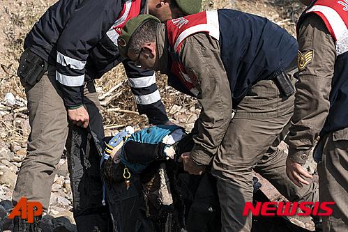 터키 경찰의 구조대가 30일(현지시간) 에게해를 건너다 배가 전복돼 사망한 시리아 난민 남자 아기의 시신을 수습하고 있다. /사진=뉴시스(AP 제공)