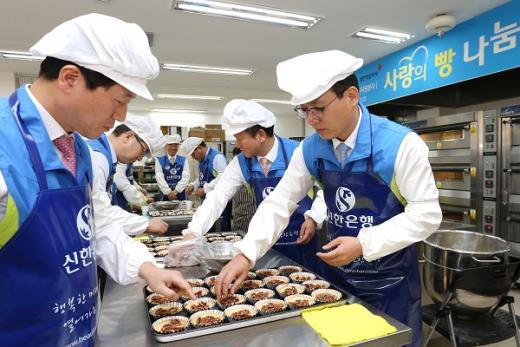신한은행 임원들이 용산구 원효로에 위치한 희망나눔 봉사센터에서 사회소외계층에 나눠줄 빵을 직접 만들고 있는 모습./사진=신한은행