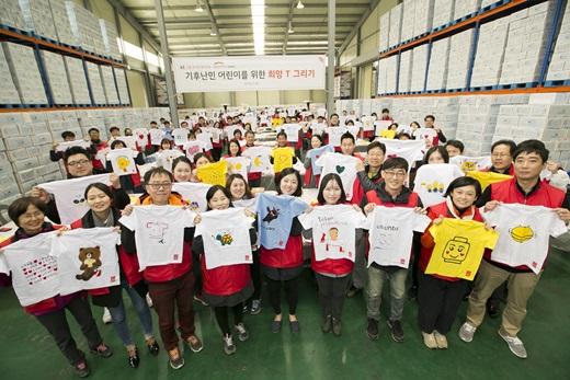KT그룹 임직원 봉사단이 기후난민 어린이를 위해 제작한 희망 티셔츠를 들고 기념사진을 촬영하고 있는 모습. /사진=KT