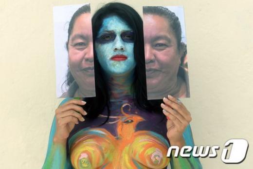 지난달 8일 몸에 페인팅을 한 엘살바도르 여성이 산살바도르에서 열린 세계 여성의 날 행사에 참석하여 지난달 4일 갱단에 의해 살해된 여성 지도자의 사진을 들고 있다. /자료사진=뉴스1