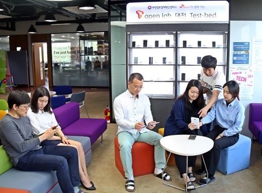 26일 대전창조경제혁신센터 내에 설치된 T오픈 랩 테스트베드에서 대전센터 및 입주 벤처업체 직원들이 테스트용 단말기를 보며 실험결과를 논의하고 있다. /사진=SK텔레콤