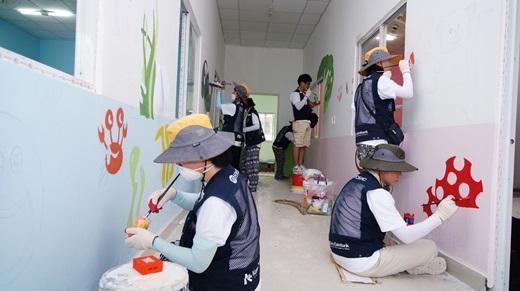 효성과 한국수출입은행 임직원들이 신축되는 흡픅(Hiep Phuoc) 유치원 복도에 그림을 그리고 있다. /사진=효성