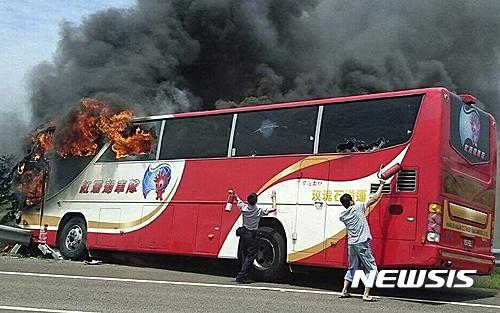 대만 버스 화재. 19일 오전 12시52분쯤(현지시간) 대만 타오위안 공항 인근 간선 도로를 달리던 버스에서 불길과 검은 연기가 치솟고 있는 가운데 경찰관과 한 남성이 승객들을 구하기 위해 소화기로 버스 유리창을 부수려 애쓰고 있다. /사진=뉴시스(AP통신 제공)