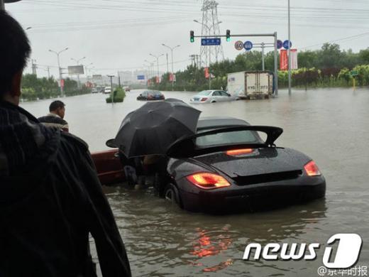 베이징 폭우. 베이징 펑타이구에 내린 비로 자동차가 물에 잠기면서 운전자가 빠져나고 있다. /자료사진=뉴스1(중국 경화시보 제공)