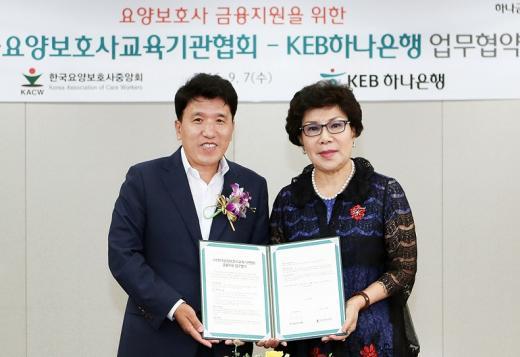 지난 7일 함영주 KEB하나은행 은행장(사진 왼쪽)과 민소현 (사)한국요양보호사교육기관협회 회장(오른쪽)이 협약서를 들고 기념촬영을 하고 있다./사진=KEB하나은행