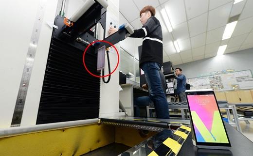 LG전자 연구원이 바닥에 깔린 철판 위로 V20를 떨어트려 내구성을 테스트하고 있다. /사진=LG전자