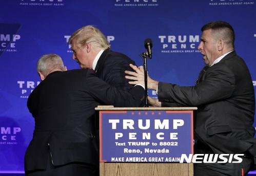 미국 공화당 대선 후보 도널드 트럼프가 지난 5일(현지시간) 네바다주 르노 유세 도중 비밀경호국(SS) 요원들에 이끌려 무대 뒤로 피신하고 있다. /사진=뉴시스(AP)