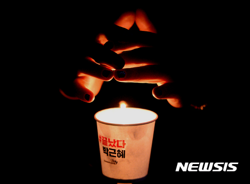 중앙일보 여론조사. 박근혜 대통령 퇴진을 촉구하는 촛불문화제가 열린 23일 오후 서울 종로구 청계광장에서 참가자가 촛불이 꺼지지 않게 손으로 막고 있다. /자료사진=뉴시스