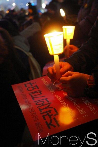 26일 오후 서울 광화문광장에서 진행 중인 5차 촛불집회에 참가한 한 시민이 '주권자의 7대 요구'라는 피켓을 들고 박근혜 대통령 퇴진을 촉구하고 있다. /사진=서대웅 기자