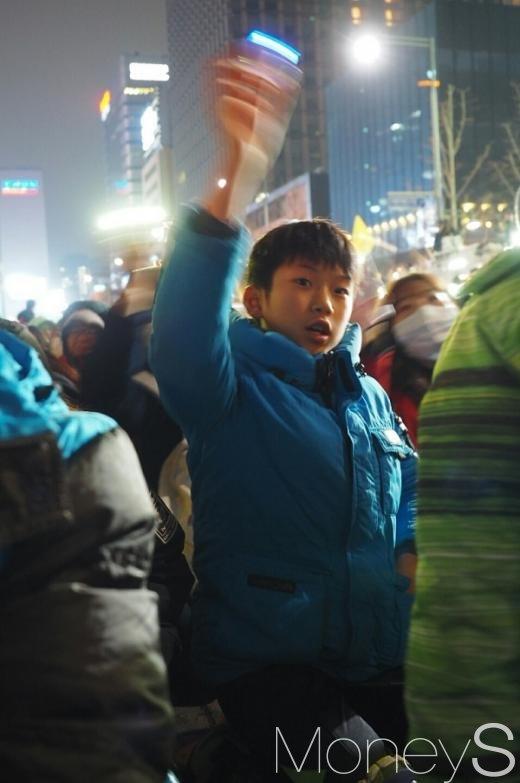 26일 오후 서울 광화문광장에서 열린 5차 촛불집회에 한 아이가 음악에 맞춰 손을 흔들고 있다. /사진=서대웅 기자