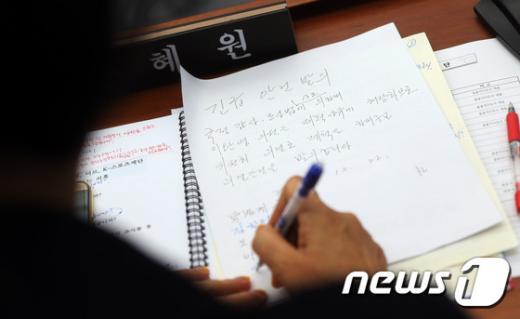 제척. 손혜원 민주당 의원이 이완영 의원 제척 요구 긴급 발의안에 서명하고 있다. /사진=뉴스1