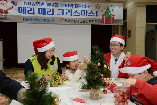 이윤배 NH농협손해보험 대표이사(뒷줄 맨 오른쪽)와 헤아림 봉사단원이 서울 서대문구 소재 서대문장애인종합복지관에서 장애아동과 성탄절 트리를 만들고 있다. /사진=NH농협손해보험