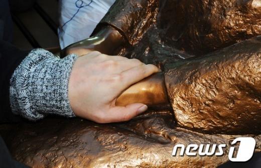 한일 통화스와프. 미래세대가세우는평화의소녀상추진위원회가 지난달 28일 부산 동구 주한 일본총영사관 앞에 '평화의 소녀상'을 기습 설치한 가운데, 한 시민이 소녀상의 손을 잡아 주고 있다. /사진=뉴스1