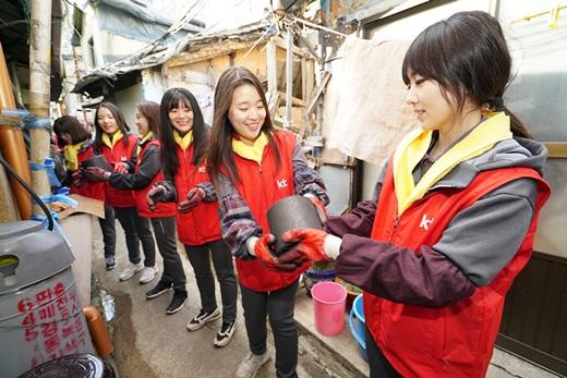 KT그룹 신입사원들이 지난 6일 부산 동구 범일5동 매축지 마을에서 주민들을 위해 총 4500장의 연탄을 전달하고 있다. /사진=KT