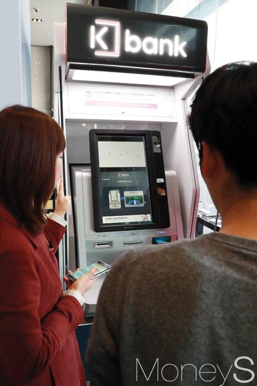 케이뱅크 직원이 현금자동입출금기 사용법을 설명하고 있다. /사진=임한별 기자