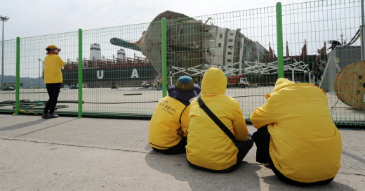 세월호 참사 희생자 유가족들이 전남 목포신항 부두펜스 앞에 앉아 세월호 세척 작업을 지켜보고 있다. /사진=뉴시스 DB
