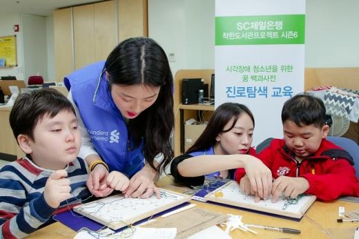 SC제일은행 직원들이 지난 12일 서울 강북구 수유동 소재 한빛맹학교에서 시각장애 청소년들을 위한 진로탐색 수업을 진행하고 있다./사진=SC제일은행
