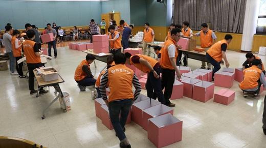 한화시스템 직원들이 지난달 31일 구미사업장에서 초록우산어린이재단과 함께 지역 여성청소년에게 제공할 여성용품을 담은 '사랑의 핑크박스'를 제작하고 있다. /사진=한화시스템