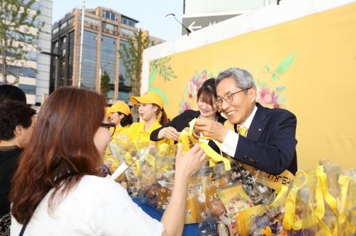 윤종규 KB국민은행장이 콘서트를 방문한 고객들에게 감사의 선물을 전달하고 있다./사진=KB국민은행